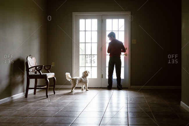 Boy with small white dog at French doors