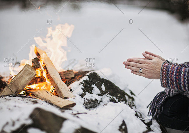 A woman warms her hands by a campfire on a cold winter day