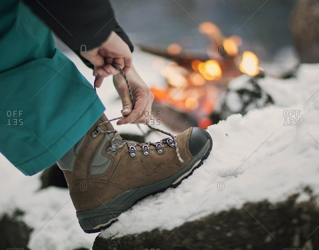A hiker ties her boots while a campfire burns in the background