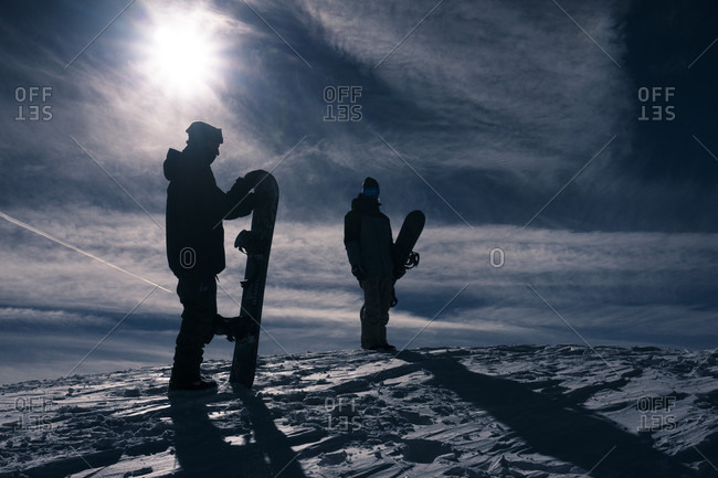 Snowboarders standing on top of a mountain
