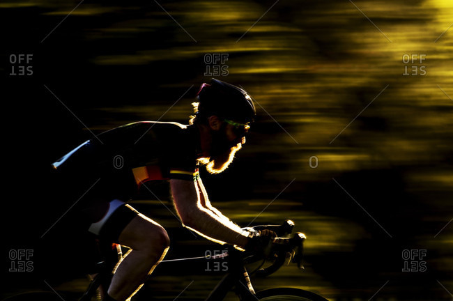 Blurred image of a bearded male cyclocross racer at speed riding through a row or trees in a race, UK