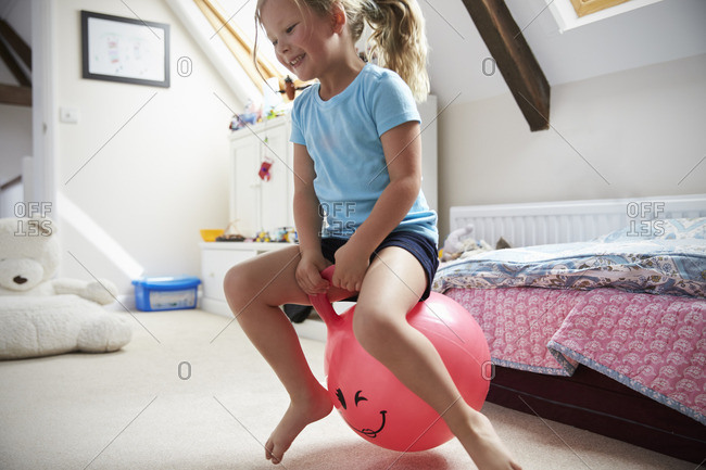 Girl bounces on inflatable ball in playroom