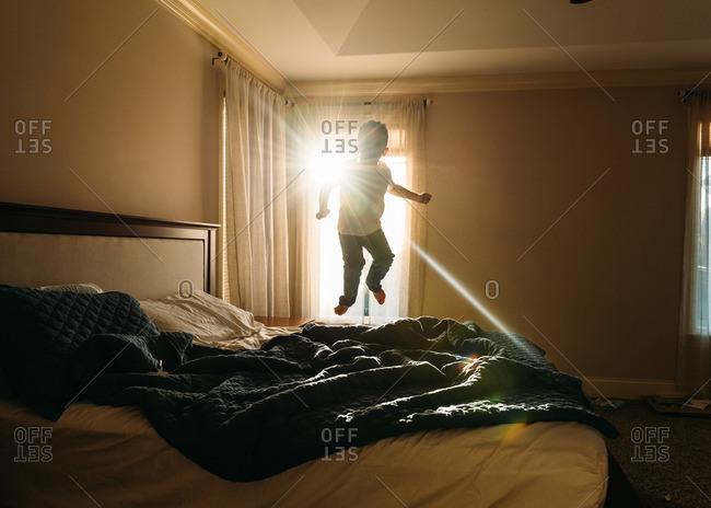 Sunlight shining through window on boy jumping on bed