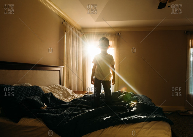 Silhouetted young boy standing on bed with sun in window