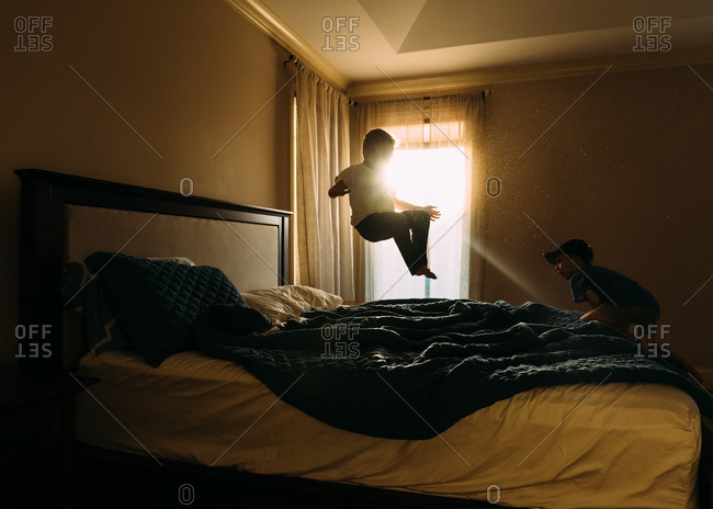 Boys playing on bed