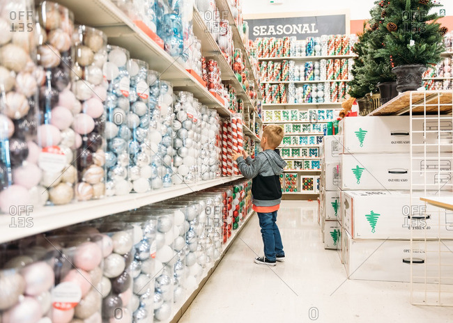 Boy in aisle of store with Christmas ornaments