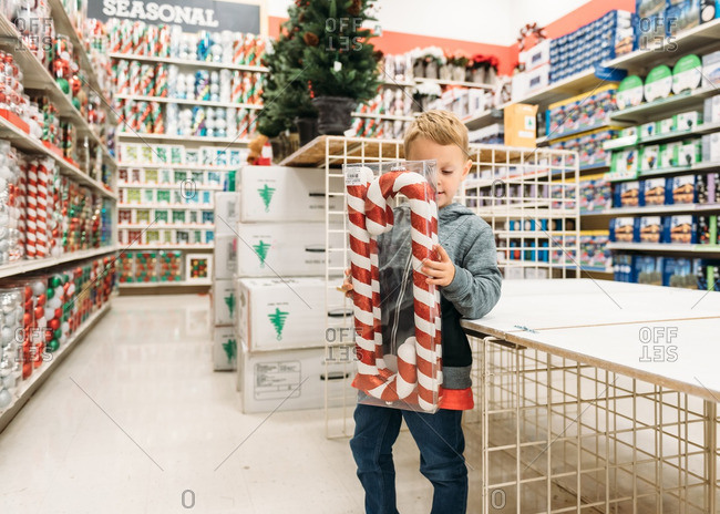 Boy holding box of candy cane Christmas ornaments