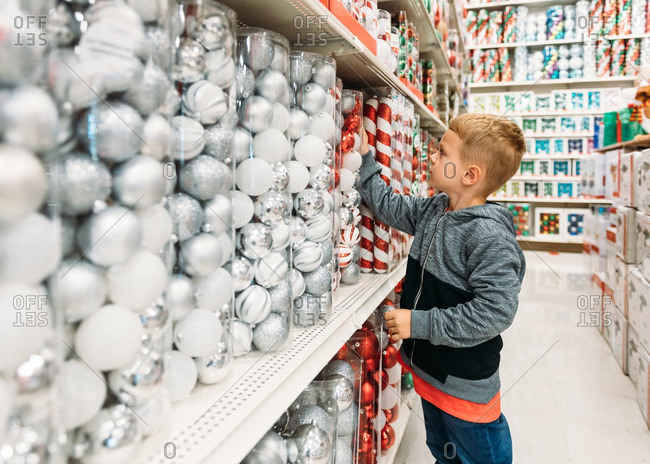 Boy in store aisle of Christmas decorations