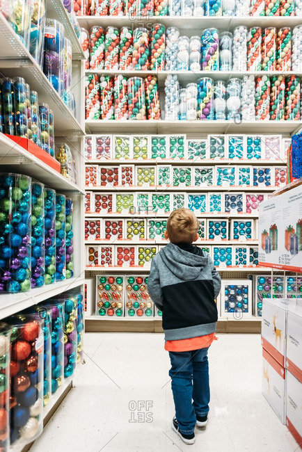 Boy standing in aisle of colorful Christmas ornaments