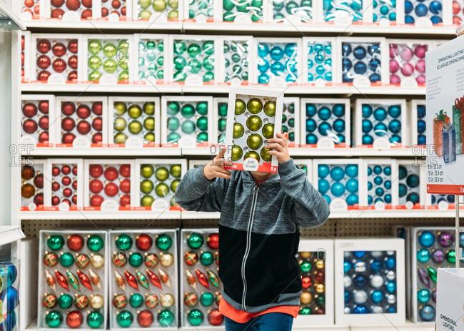 Boy holding box of green Christmas balls