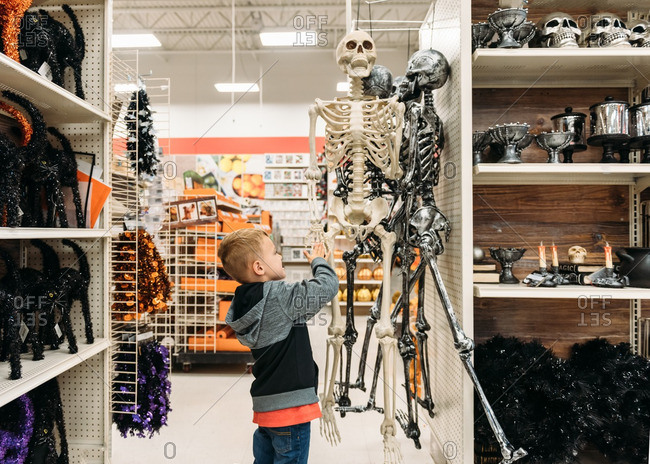 Boy looking at plastic skeleton Halloween decorations in store