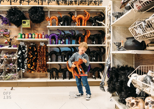 Boy with orange tinsel cat decoration in Halloween aisle of store
