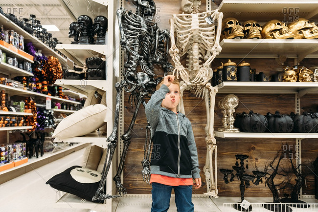 Boy fascinated by Halloween skeleton decoration in store