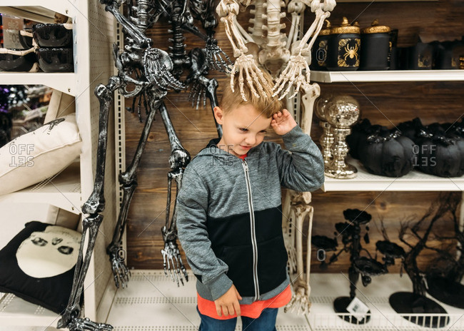 Boy with plastic skeleton hands on his head