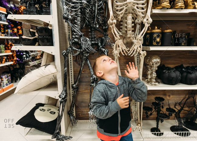 Young boy playing with plastic Halloween skeleton in store