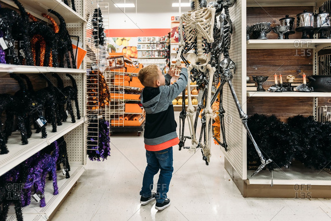 Boy examining the hands of a Halloween skeleton decoration
