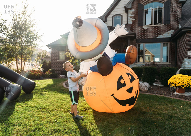Boy playing with inflatable decorations in front yard