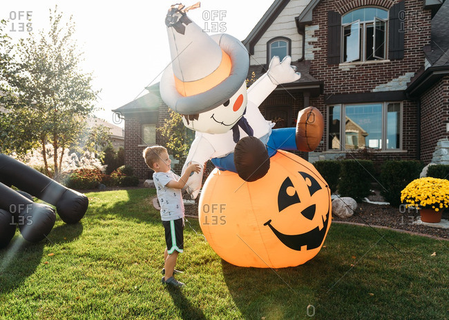 Boy playing with inflatable Halloween decorations in front yard