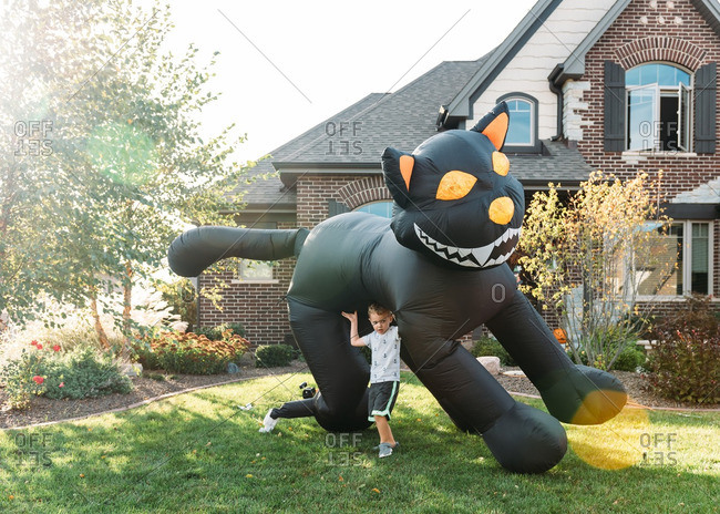 Boy playing underneath an inflatable black cat in front yard