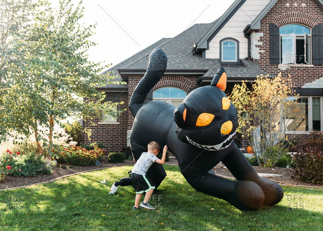 Boy playing with an inflatable black cat decoration in yard