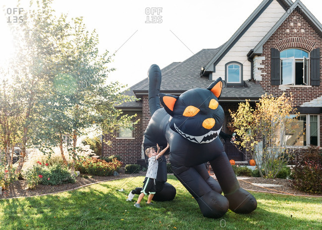 Boy pushing on inflatable Halloween decoration in front yard