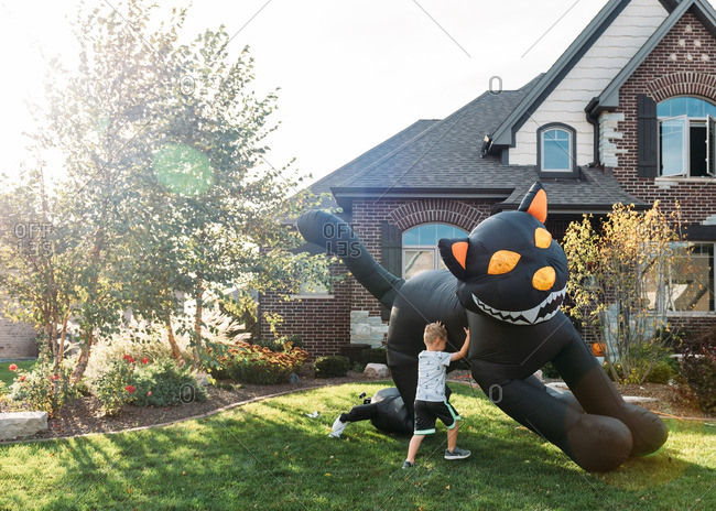Boy setting up inflatable Halloween decoration in front yard