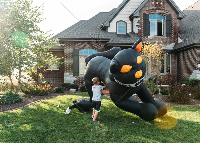 Boy setting up inflatable black cat decoration in front yard