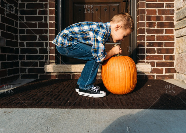Boy attempting to lift a heavy pumpkin on front porch