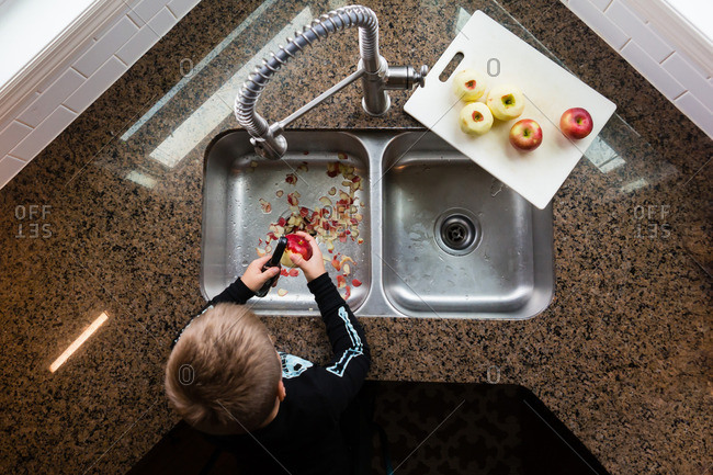 Overhead view of boy peeling apples at sink