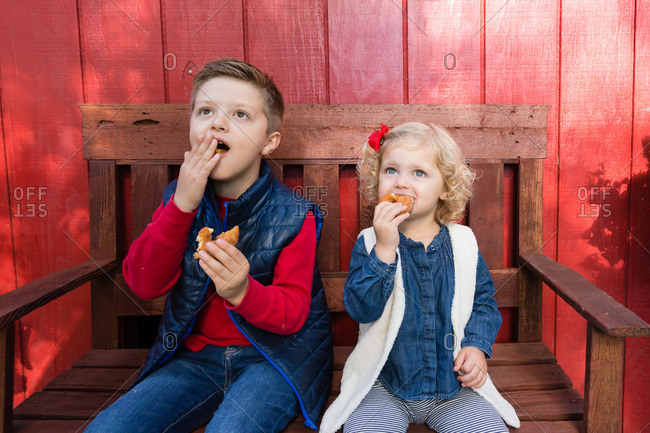 Two children eating donuts on bench