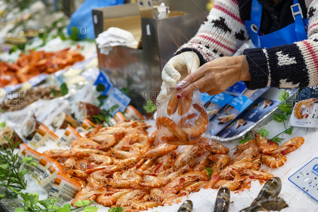 Paris, France - September 17, 2016: Woman bagging shrimp at Marche des Enfants Rouges, Marais