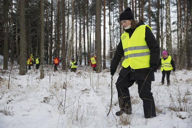 Sweden, Uppland, Upplands Vasby, Volunteers of Missing people organization in winter forest