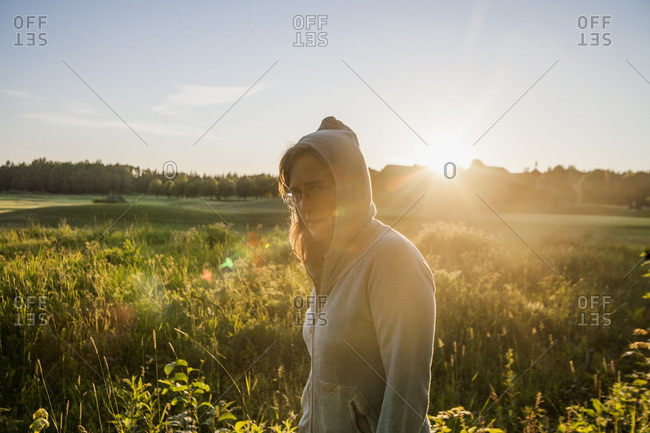 Sweden, Uppland, Orbyhus, Woman wearing hooded shirt by field at sunset