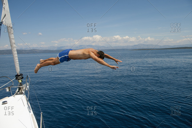 Croatia, Man diving into sea from bow of sailboat