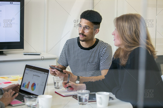 Sweden, Woman and man sitting at desk in office