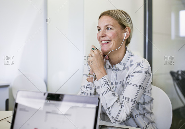 Sweden, Smiling woman with headphones working at desk