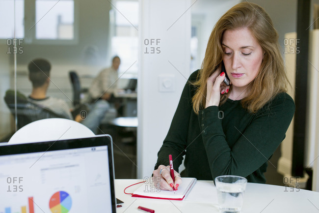 Sweden, Woman using phone and writing in notebook in office