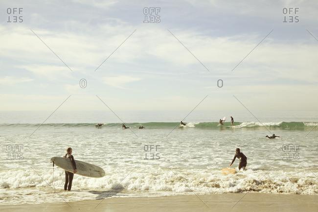 USA, California, Los Angeles,  - January 18, 2014: Venice, Surfers wading in sea