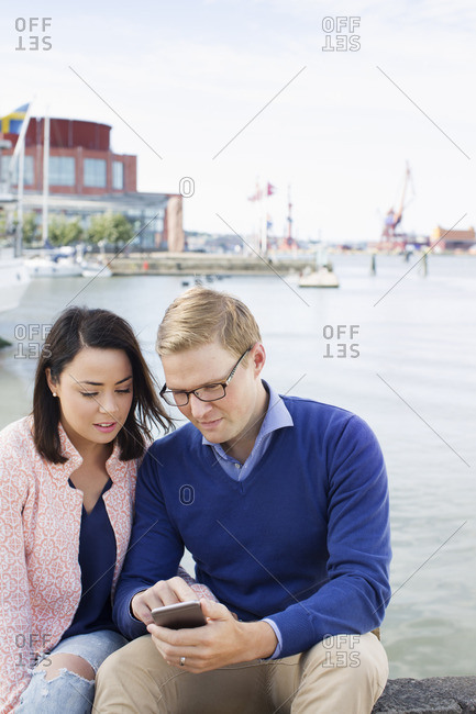 Sweden, Vastergotland, Gothenburg, Young couple sitting by harbor and checking smart phone