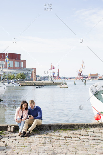 Sweden, Vastergotland, Gothenburg, Young couple sitting on promenade at harbor and checking smart phone