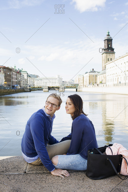 Sweden, Vastergotland, Gothenburg, Young couple sitting on promenade by canal