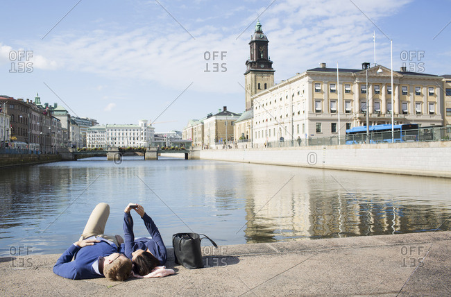 Sweden, Vastergotland, Gothenburg, Young couple lying on promenade and taking selfie