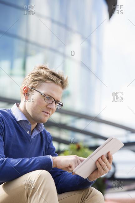 Sweden, Vastergotland, Gothenburg, Young man sitting against glass building and using digital tablet