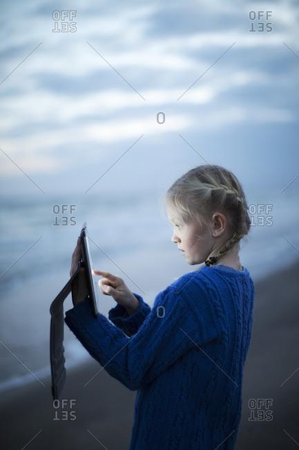 Sweden, Skane, Osterlen, Malarhusen, Borrbystrand, Girl using tablet on beach at dawn