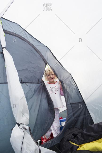 Sweden, Smiling girl in pajamas standing in grey tent