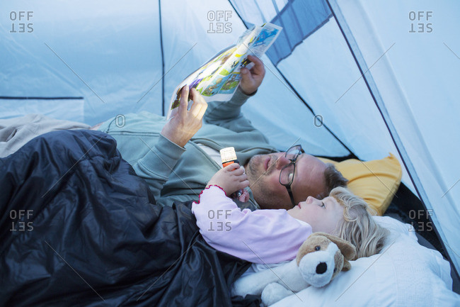 Sweden, Father and daughter reading comic book in tent