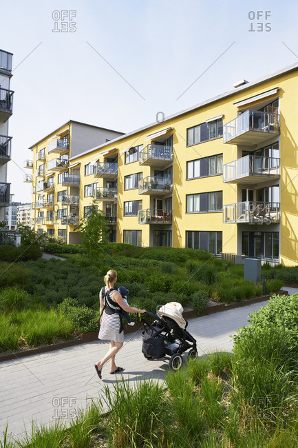 Sweden. Sodermanland, Hammarby Sjostad, Woman pushing baby carriage