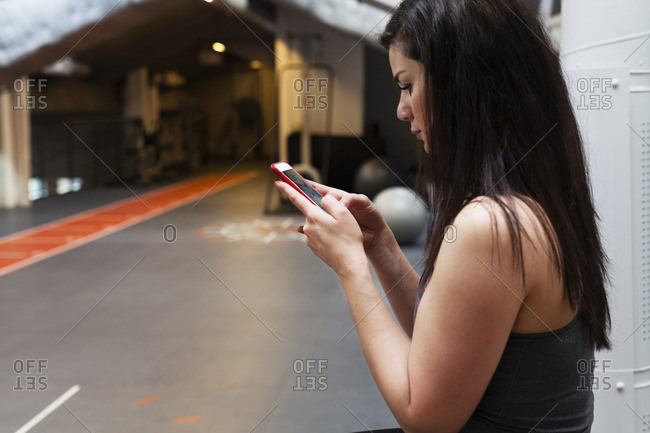 Sweden, Young woman texting at gym