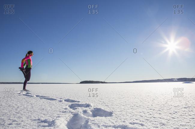 Sweden, Medelpad, Sundsvall, Woman running on snowy day