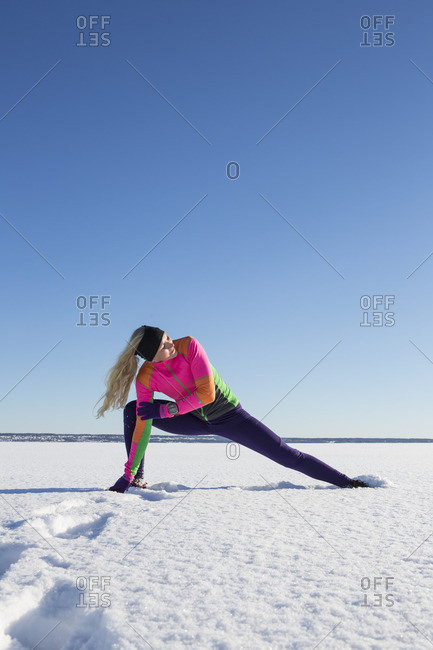 Sweden, Medelpad, Sundsvall, Woman stretching on snowy day